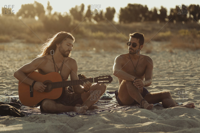Relaxed talented man playing acoustic guitar for male friend while sitting together on sandy beach at sunset