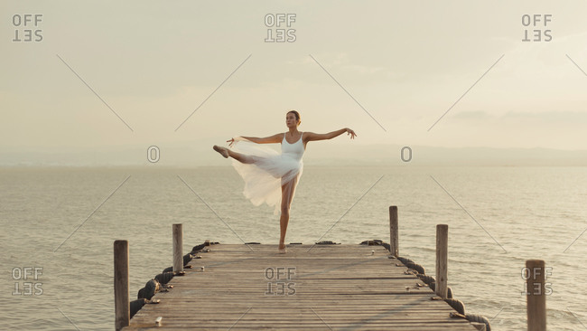 Full body young graceful female dancer in white gown standing on tiptoes with leg raised while performing ballet movements on wooden boardwalk against sea in summer evening