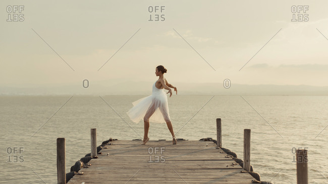 Full body young graceful female dancer in white gown standing on tiptoes while performing ballet movements on wooden boardwalk against sea in summer evening