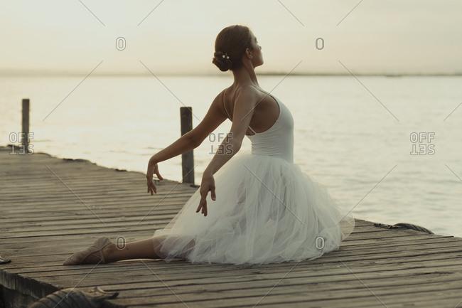 Full body flexible classic ballet female dancer in elegant white dress performing sensual pose on wooden pier against blurred sea in summer evening