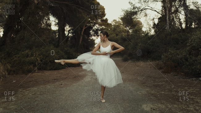 Full body talented young female ballet performer in white dress and pointe shoes dancing with leg outstretched on path in green forest in summer evening