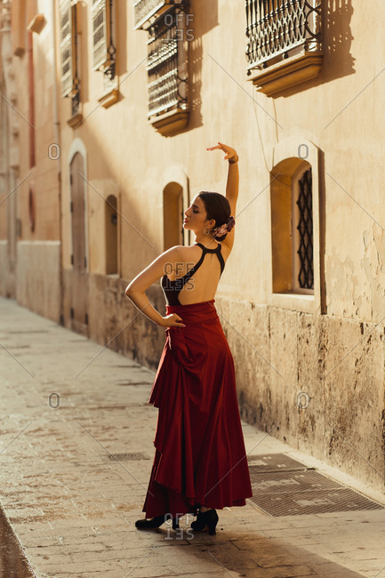 Full body back view of young Hispanic female dancer in traditional outfit performing Flamenco dance on old street with aged stone buildings