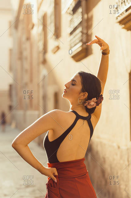 Back view of young Hispanic female dancer in traditional outfit performing Flamenco dance on old street with aged stone buildings