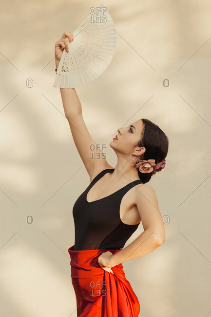 Side view of Hispanic female Flamenco dancer with white fan performing passionate dance near white wall