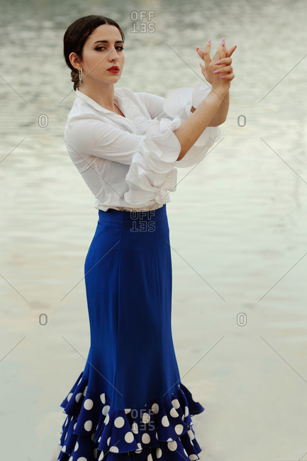 Side view of sensual young Hispanic woman in elegant white blouse and blue skirt performing graceful movements with hands during Flamenco dance against lake water