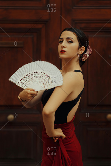 Side view of Hispanic female Flamenco dancer with white fan performing passionate dance near wooden door