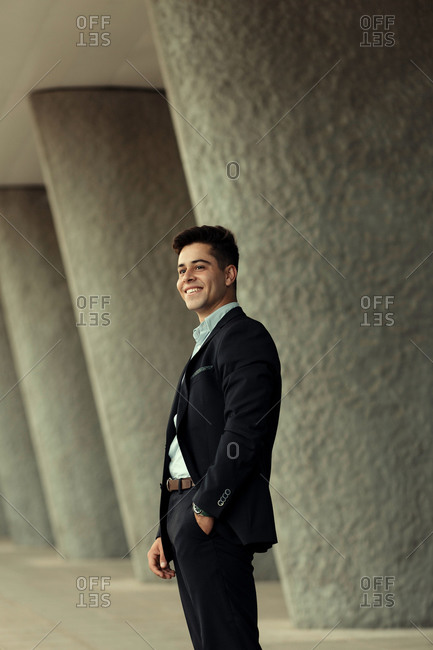 Side view of content handsome businessman standing with hand in pocket near building in city and looking away