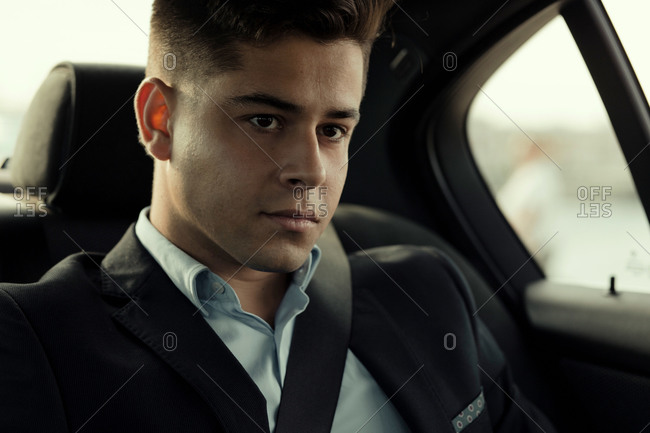 Male executive manager sitting in modern car going to work looking away