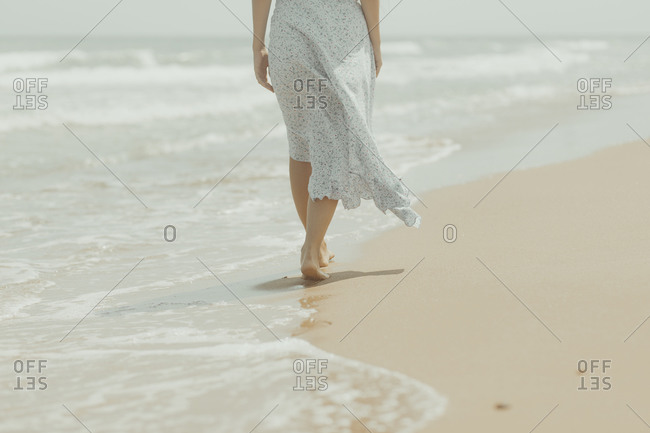 Back view of crop unrecognizable barefoot female in white summer dress walking alone on sandy beach in sunny summer day in Spain