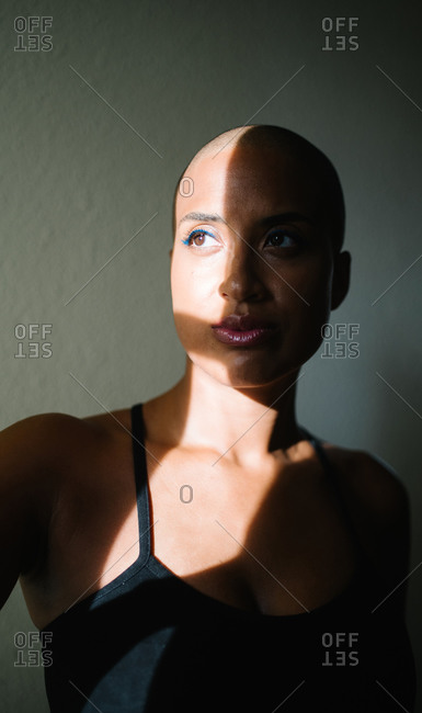 Thoughtful African American female with bald hairstyle standing near window in apartment and illuminated by sunbeam in morning