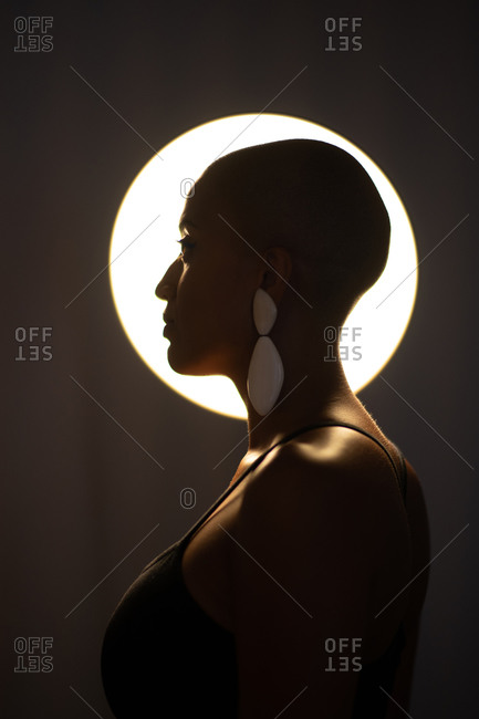 Side view of calm African American female with bald haircut and in trendy earrings standing in dark studio on background of round glowing lamp