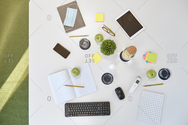 Top view of office desk with various gadgets and notebooks with medical mask prepared for business meeting and coworking during coronavirus pandemic