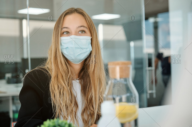 Female specialist in formal clothes wearing protective mask during work in contemporary coworking office