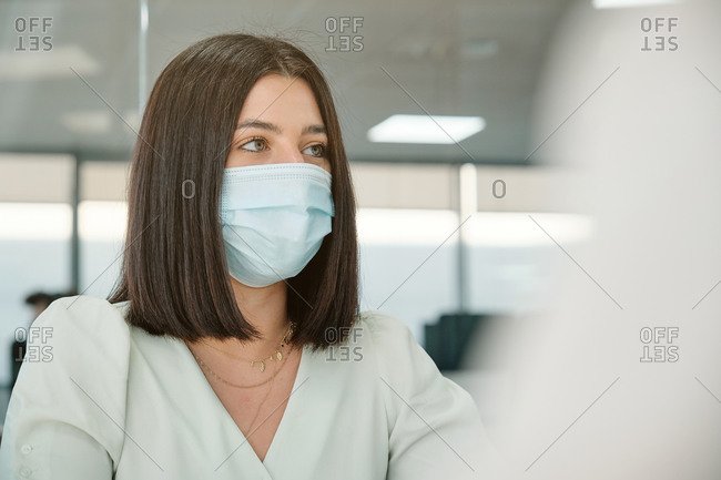 Focused female office employee in protective mask using computer while working in modern office during coronavirus pandemic