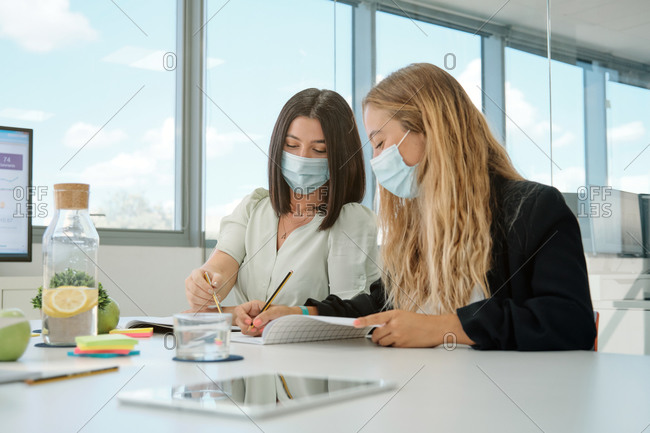 Positive young female colleagues in medical masks for coronavirus prevention taking notes in notebook and discussing details of business project while having meeting in contemporary workspace