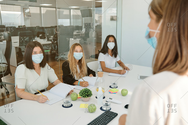 Young female manager in medical mask explaining business idea to coworkers while standing together in modern workspace and discussing project