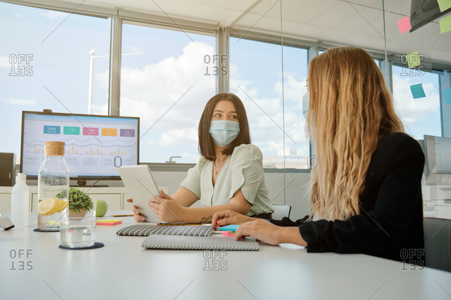 Serious young female coworkers in medical masks sitting at table with gadgets and papers and having conversation about business results during meeting in spacious office room