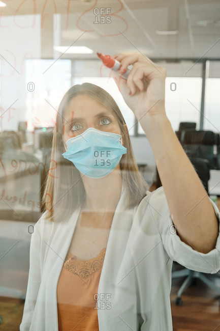 Young female member of business team in protective mask taking notes on glass wall while working with colleagues and searching for solution of business problem in contemporary office