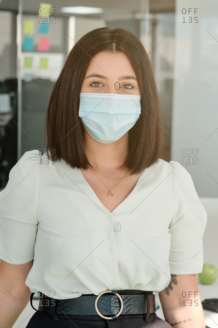 Positive young female specialist in protective mask looking at camera while standing in modern workspace