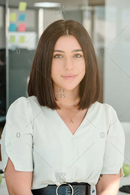 Positive successful young woman in stylish outfit looking at camera while standing in contemporary workspace