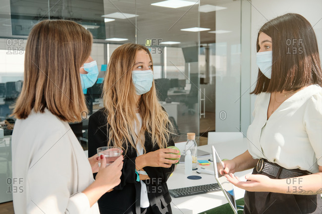 Group of modern young female colleagues in protective masks gathering in contemporary workspace and discussing business ideas while working together during coronavirus pandemic