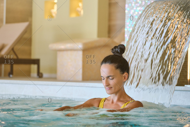 Positive young female getting hydrotherapy massage under waterfall during spa session in pool of luxury spa center in resort
