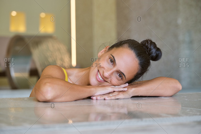 Happy young female looking at camera and smiling while relaxing during spa session with hydro massage in modern wellness center