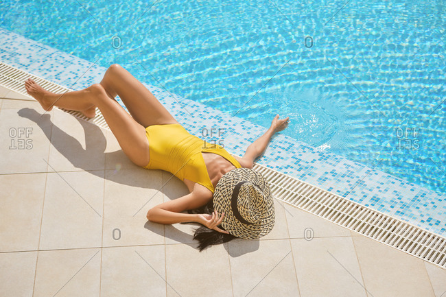 From above full body of unrecognizable slim female in swimsuit and hat lying near swimming pool with clear blue water and enjoying summer holidays in resort