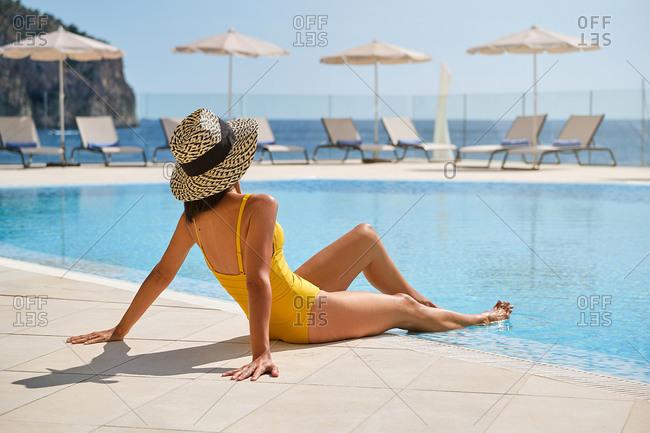 Full length of slim female traveler in swimwear and hat sunbathing at poolside and enjoying sunny day while spending summer holidays in resort