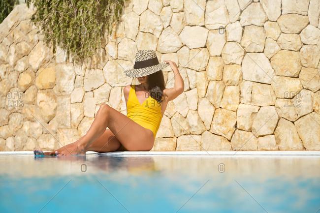 Full length of cheerful slim female traveler in swimwear and hat sunbathing at poolside and enjoying sunny day while spending summer holidays in resort