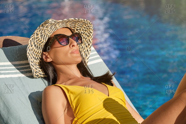 Stylish young female in swimwear and hat lying on sunbed near swimming pool and enjoying summer holidays in luxury resort