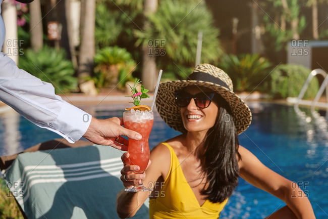 Cheerful young female tourist in stylish straw hat and sunglasses receiving fresh cold fruit beverage from unrecognizable barmen while enjoying summer vacation at poolside in resort