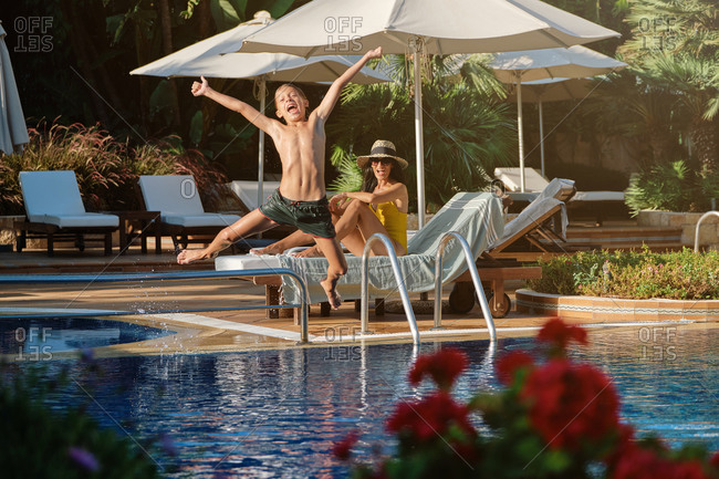 Cheerful boy having fun and jumping into swimming pool while mother resting on lounge chair at poolside during summer vacation together in resort