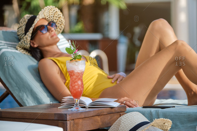 Side view of young female in swimsuit and straw hat with sunglasses relaxing on lounge with book and glass of cold beverage while spending summer holidays in luxury resort