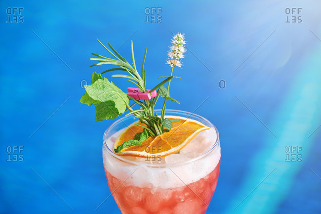 Glass of delicious cold fruit drink with orange slice and herbs placed at poolside against blue water of swimming pool in summer day