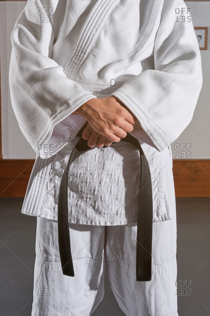 Cropped unrecognizable person standing with the arms crossed in a kimono with a black belt tied around his waist. Martial arts concept