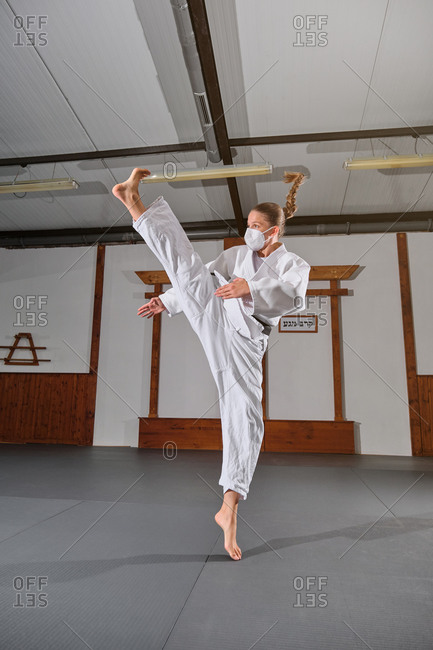 Woman with a white kimono and braid wearing a protective face mask with a black belt tied up kicking in the air in a martial arts gym