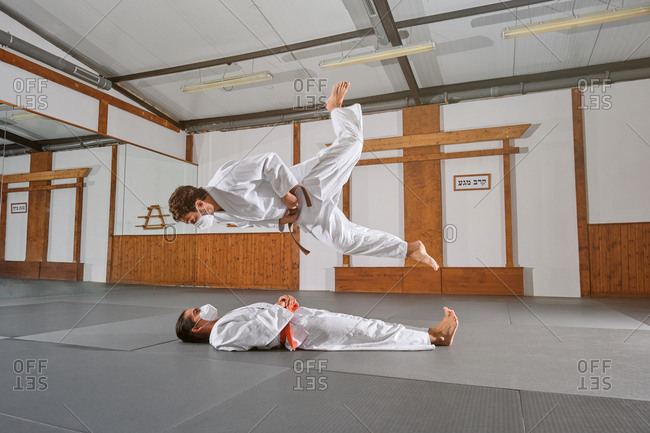 Side view of two people with mask and kimono practicing krav maga while one jumps on top of the other in a gym