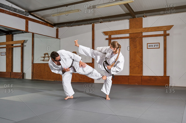Two people with mask and kimono practicing krav maga kicks during a combat in a gym