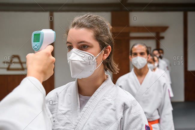 Row of people wearing masks and a kimono taking the covid temperature test in a krav maga gym