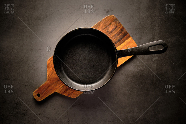 Top view of metal frying pan placed on wooden cutting board on table in kitchen