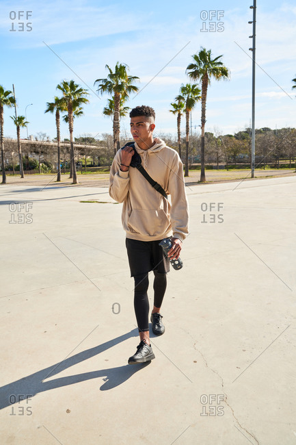Full body confident young ethnic male athlete in sportswear with bag over shoulder and bottle of drink in hand walking on paved square in sunny summer day