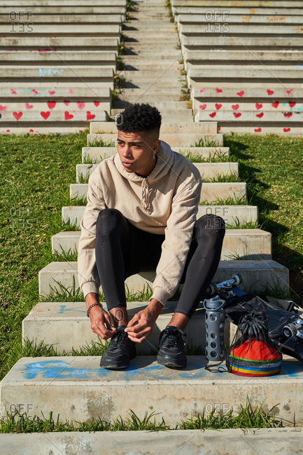 Serious young ethnic sportsman in activewear sitting on concrete stairs and tying shoelaces while preparing for workout