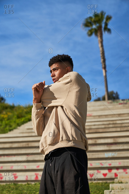 Low angle full body of confident young ethnic sportsman in activewear standing on concrete steps and doing exercises while warming up before training