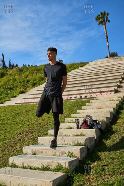 Low angle full length of young athletic male in sportswear stretching leg while doing exercises on stairs and warming up before running in park in sunny summer day
