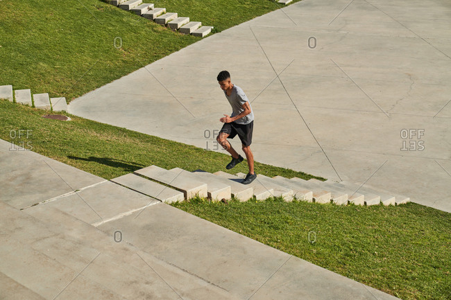 Full body side view of determined young ethnic sportsman running up stairs during intense fitness workout in sunny summer day