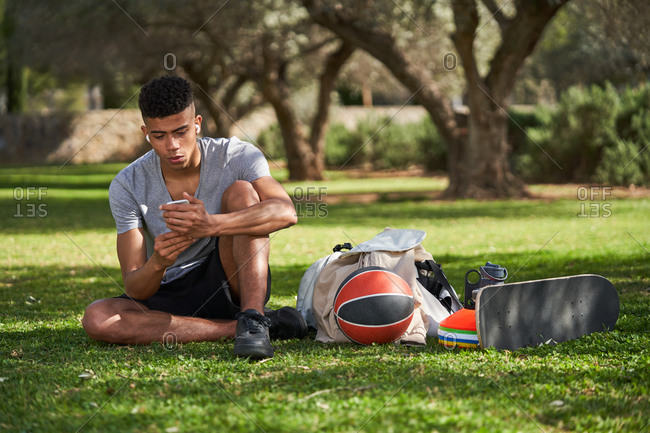 African American sportsman sitting on lawn with basketball and skate while relaxing after training and chatting on social media via mobile phone