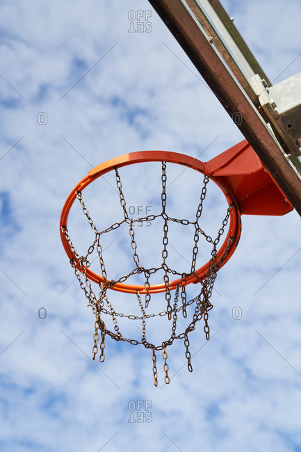From below of street basketball hoop with chain net on sports ground against blue cloudy sky