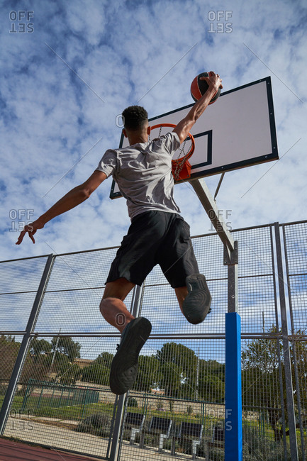 From below of African American male player jumping and scoring ball in basketball hoop during game on sports ground