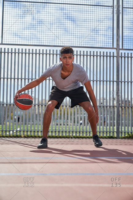 Determined ethnic male player practicing with basketball on modern court in summer while looking forward